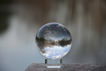 Park Landscape, Lake And Blue Sky Refracted In A Crystal Lens Ball