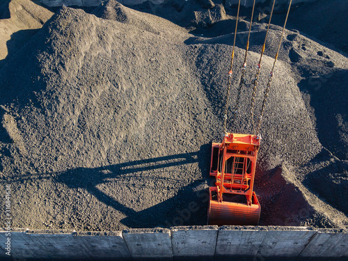 Coal lies in heaps fenced with concrete massifs and a clamshell bucket of a gantry crane for loading Tapéta, Fotótapéta