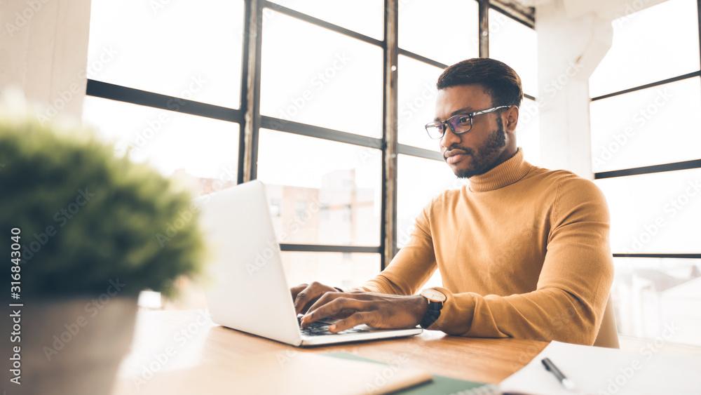 Fototapeta Afro man working on laptop in modern office