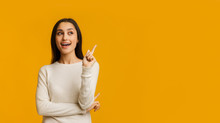 Young Brunette Woman Pointing Finger Up, Having Idea Over Yellow Background