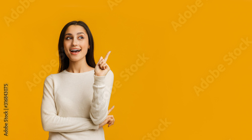Young Brunette Woman Pointing Finger Up, Having Idea Over Yellow Background Fototapeta