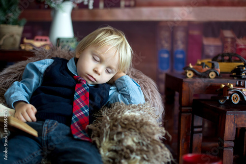 Fotografie, Obraz Sweet toddler boy, fall asleep on little baby couch while reading book at home