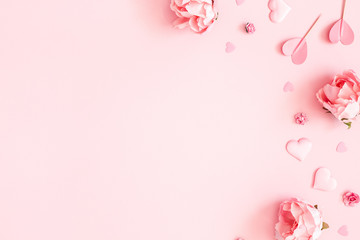 Valentine's Day background. Pink flowers, envelope, hearts on pastel pink background. Valentines day concept. Flat lay, top view, copy space
