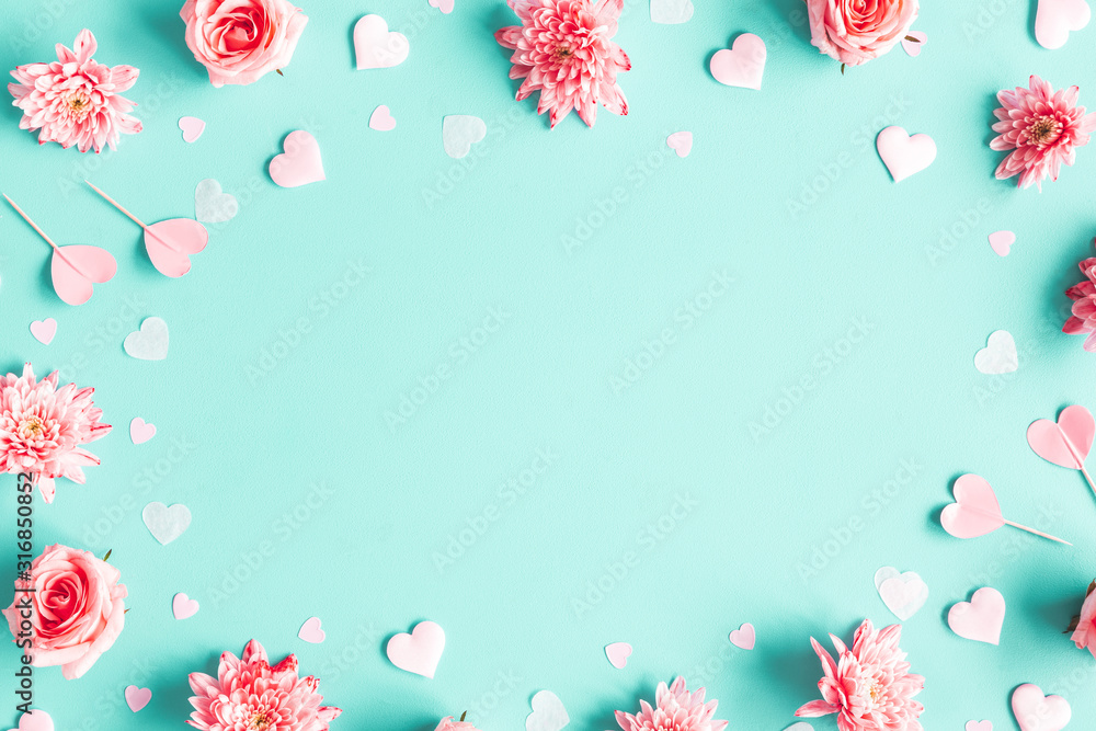 Fototapeta Valentine's Day background. Pink flowers, hearts on pastel blue background. Valentines day concept. Flat lay, top view, copy space