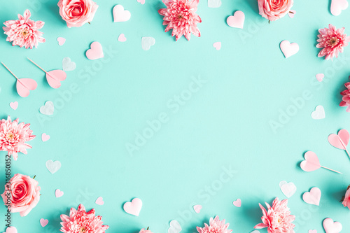 Obraz Valentine's Day background. Pink flowers, hearts on pastel blue background. Valentines day concept. Flat lay, top view, copy space - fototapety do salonu