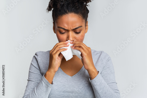 Fotografía  Woman touching her nose with napkin, having runny nose