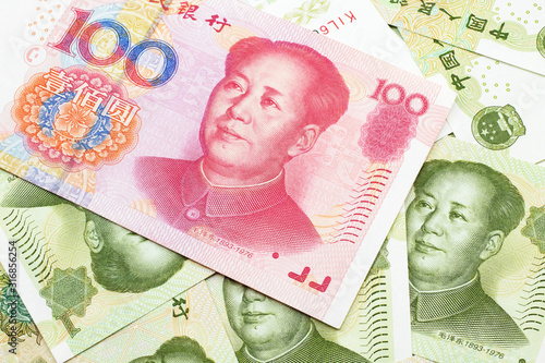 Fotografia, Obraz A close up image of a red, one hundred Chinese yuan bank note, close up on a background of green one yuan bank notes