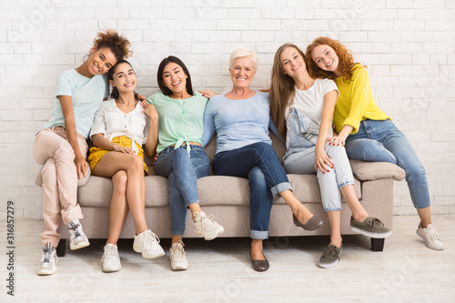Fototapeta Women Of Different Age Sitting On Sofa Smiling Indoor obraz