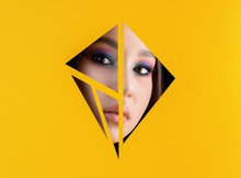 Beautiful Young Girl With Make Up Looking Through Triangles In Yellow Paper Background.
