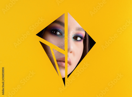 Beautiful young girl with make up looking through triangles in yellow paper background Wallpaper Mural