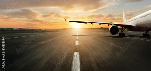 Parked airplane on runway with dramatic sunset
