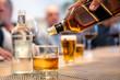 Una mano sirve un whisky. En el fondo, una botella de agua y dos cervezas. Fondo borroso. Reunion de amigos en un restaurante