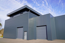 Modern New Grey Warehouse Hangar Exterior With Gray Sectional Gate
