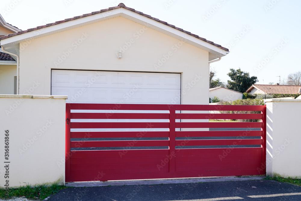 Fototapeta steel big red metal gate fence on modern house street