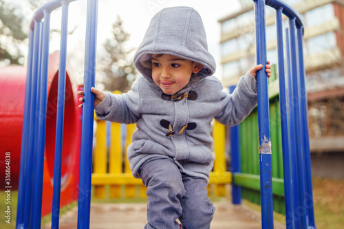 Fototapeta Portrait of small little caucasian boy kid wearing winter coat walking standing on the slide playground in the park with hood on his head in winter day smiling obraz