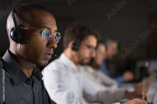 Obraz Concentrated call center operator communicating with client. African American young man in eyeglasses looking at laptop while serving client. Call center concept - fototapety do salonu