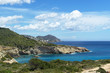 Rocky sea coast with clean blue water, cloudy sky and city view. Ibiza island, Spain
