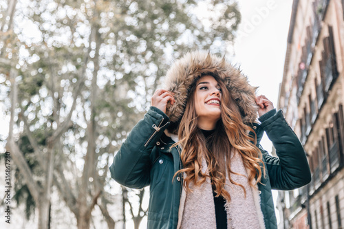 Cuadros en Lienzo  Portrait of beautiful caucasian blonde girl with coat, scarf and a big hood on a