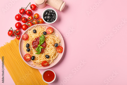 Obraz Plate with tasty pasta, olives and tomato sauce on color background - fototapety do salonu