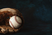Moody Style Baseball Background With Old Ball In Leather Glove Close Up For Sport, Copy Space On Dark Backdrop.