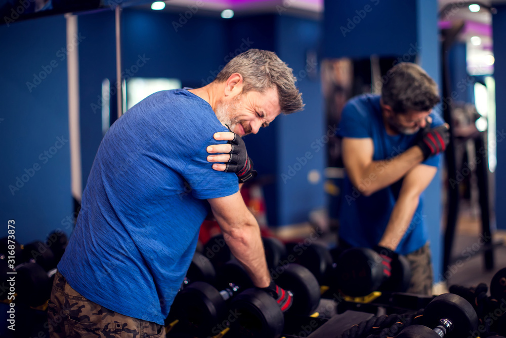 Fototapeta Man feeling strong shoulder pain while training with dumbbells in the gym. People, fitness and healthcare concept
