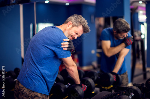 Vászonkép Man feeling strong shoulder pain while training with dumbbells in the gym