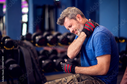 Man feeling strong neck pain while training in the gym Fototapete