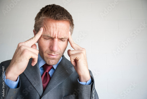 Stressed businessman rubbing his temples with eyes closed to alleviate his heada Canvas Print