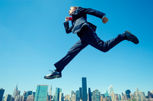 Giant Businessman Jumping In B...