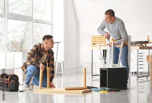 Handymen assembling furniture in workshop Wallpaper Mural
