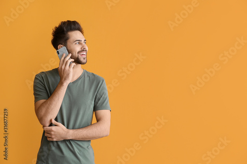 Fotomural Happy young man talking by mobile phone on color background