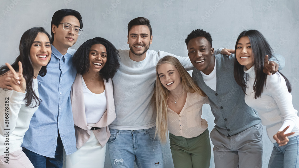 Fototapeta Portrait of happy young business team posing over grey background