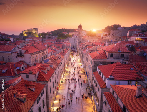 Aerial view of beautiful old city at sunset. Top view of houses with red roofs, city lights, historical centre, architecture, walking people in illuminated streets at night in Dubrovnik, Croatia