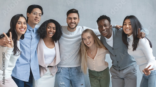 Obraz Portrait of happy young business team posing over grey background - fototapety do salonu