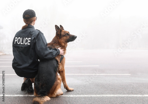 Photo Female police officer with dog patrolling city street