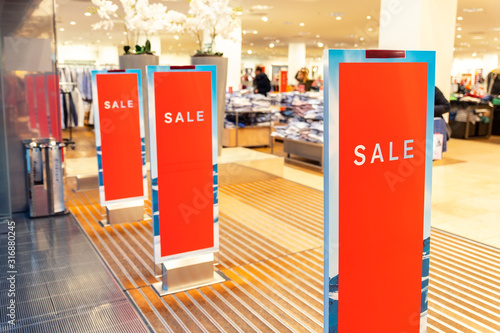 Photo Red bright sale banner on anti-thieft gate sensor at retail shopping mall entrance