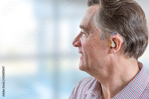 head of a senior man with hearing aid in his ear Canvas Print