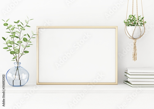 Fotografía Interior poster mockup with horizontal gold metal frame on the table with plants in blue vase and hanging macrame pot on empty white wall background