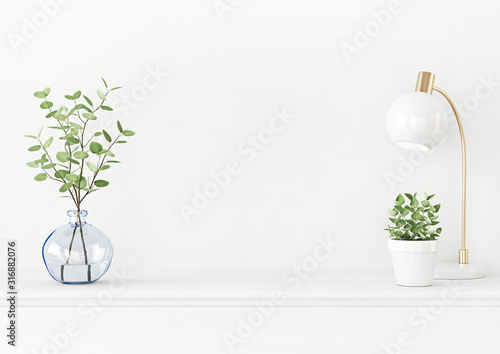 Photo Interior wall mockup with branches in blue vase, lamp and green plant in pot on empty white background