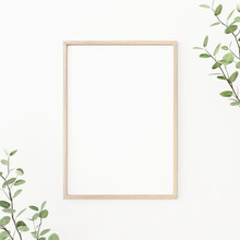 Interior Poster Mockup With Vertical Wooden Frame On Empty White Wall, Decorated With Plant Branches With Green Leaves. A4, A3 Size Format. 3D Rendering, Illustration.