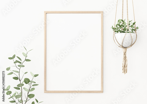 Obraz Interior poster mockup with vertical wooden frame on empty white wall decorated with plant branch and hanging macrame pot. A4, A3 size format. 3D rendering, illustration. - fototapety do salonu