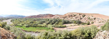Panoramic View Of Azro In The Atlas Mountains Foothills In Morocco. A River Winds Past The Village In The Foreground With Green Vegetation Growing, And In The Background Is Dry Rocky Desert Landscape.