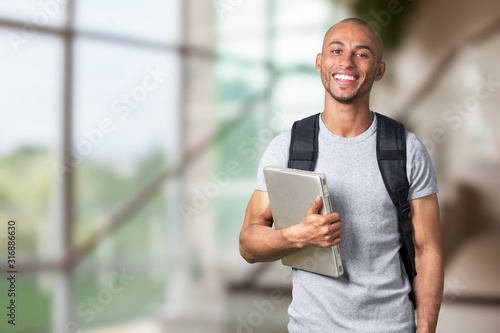 Photo Smiling young black college student with laptop
