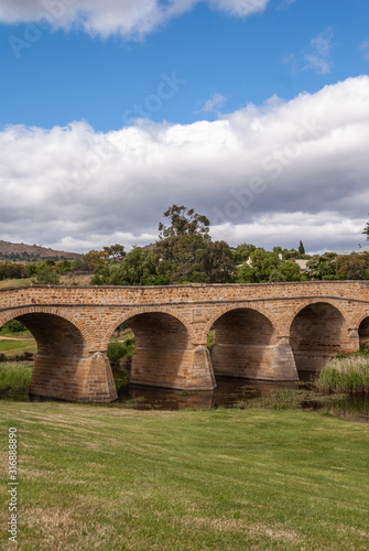 Richmond, Tasmania, Australia - December 13, 2009: Distance portrait of brown stone historic bridge over coal river. Green foliage on shore and in water. blue and white Cloudscape.
