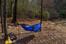 Hiker Resting In Blue Hammock In The Forest