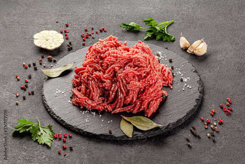 Fototapeta Raw meat products. Veal or mixed homemade minced meat with spices on a black background. board background image, copy space text obraz