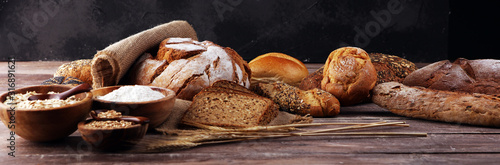 Fototapeta Assortment of baked bread and bread rolls and cutted bread on table background obraz
