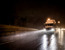 Big Rig White Semi Truck Transporting Cargo In Semitrailer Driving On The Night Wet Road With Heavy Rain And Water Dust