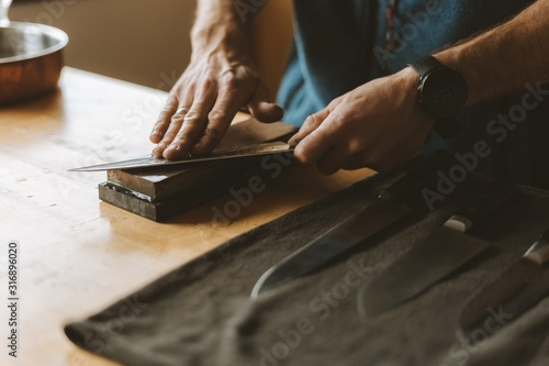 Papel de parede Person sharpening knives with a whetstone in the kitchen