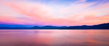 Wide Background Panorama Of A Brilliant Colorful Sky Reflecting Off Water At Sunset